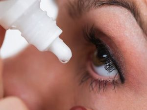 Close up of person pouring eye drops into eye