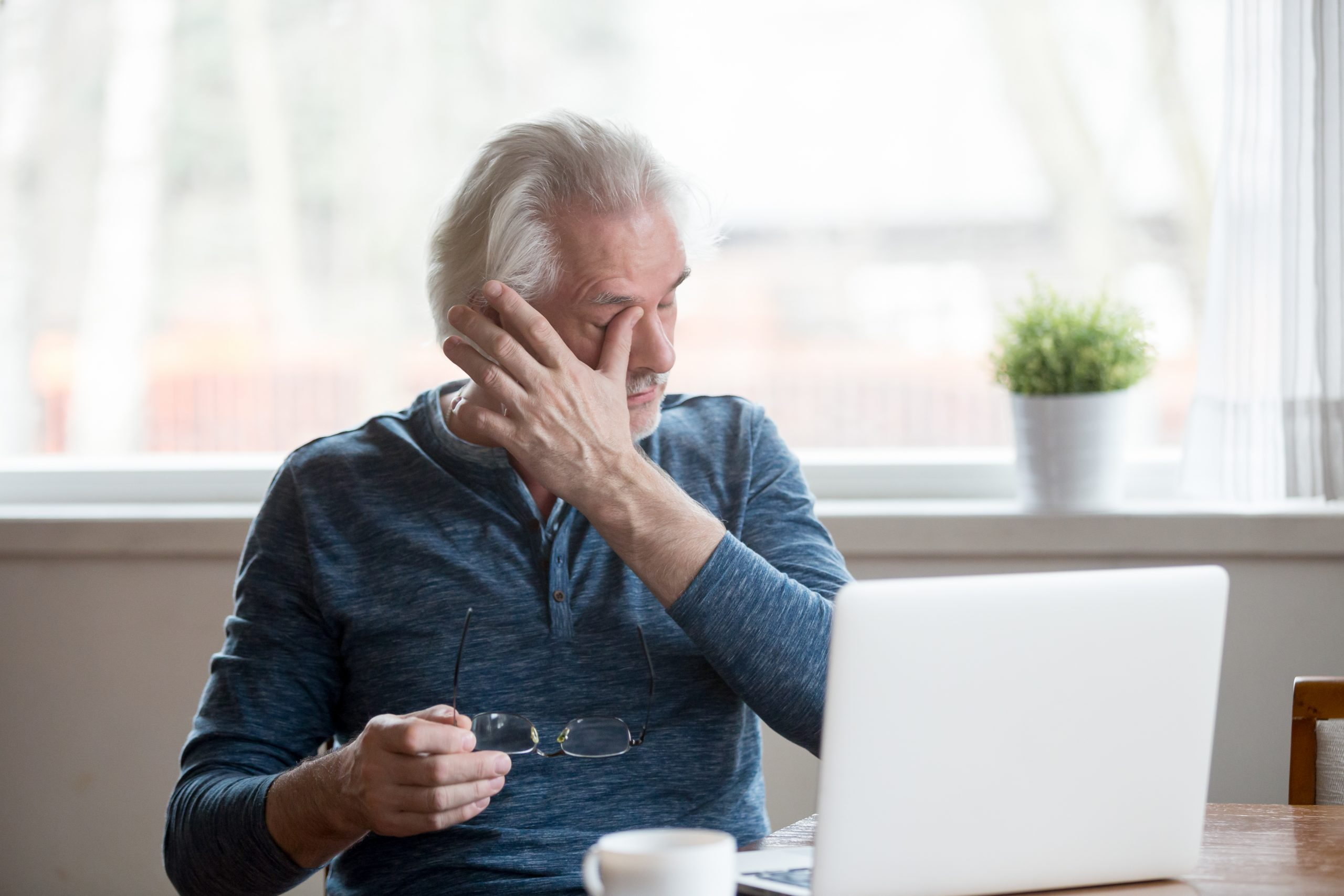 Fatigued mature old man taking off glasses suffering from tired dry irritated eyes after long computer use